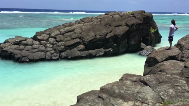 Young woman looks at the black rock in Rarotonga Cook Islands