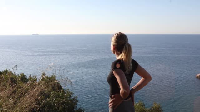 Junge Frau schaut bei Sonnenaufgang von Küstenabhang ab
