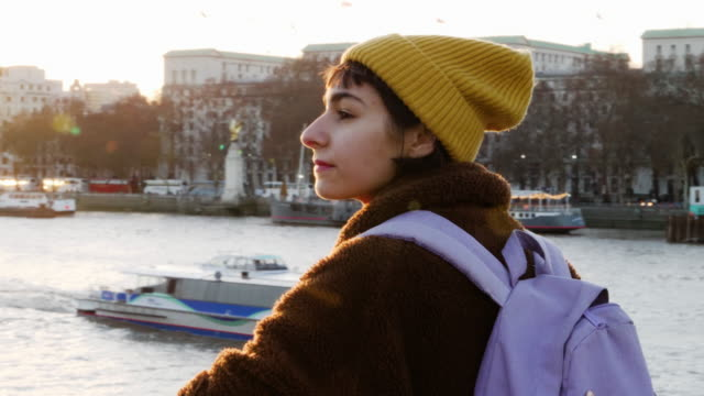 young woman looks over river thames. - turismo urbano video stock e b–roll