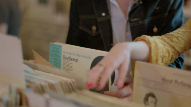 Young woman looks through vinyl albums with friends and nods to music in record store
