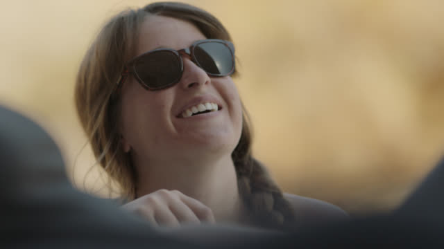 young woman looks up and smiles on moab road trip with friends. - guardare in su video stock e b–roll