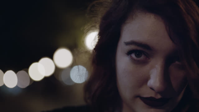 CU SLO MO. Young woman looks up and stares at camera under city streetlights.