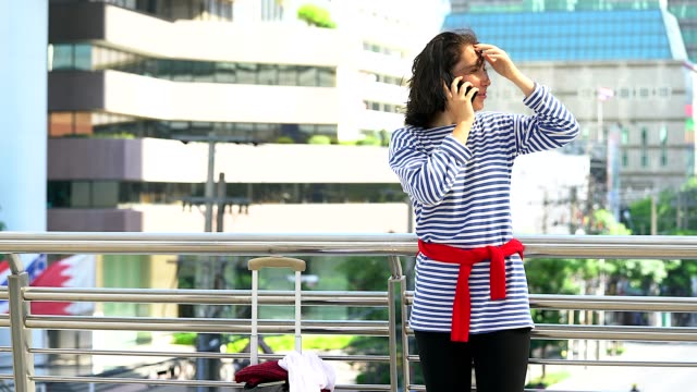 Young woman loss her wallet.She is calling to someone with city building as background.