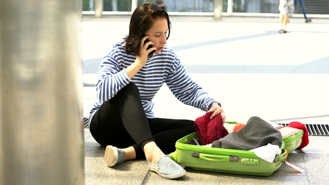 A young woman lost her passport. She is calling to someone in the city building as background.