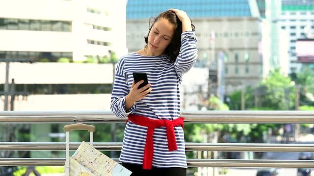 A young woman lost the way. She is looking the map on the mobile phone in the city building as background.
