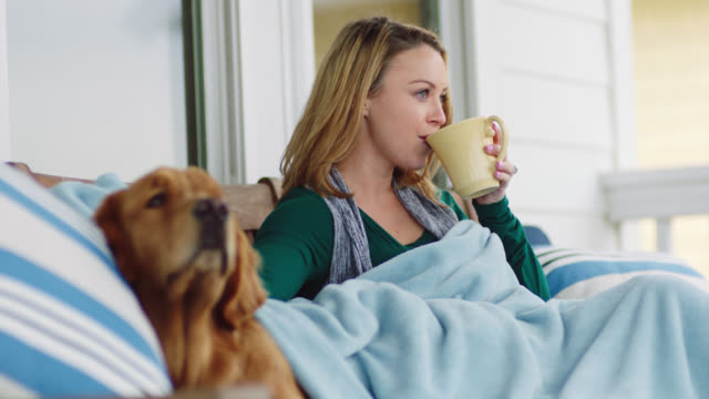 SLO MO. Young woman lovingly pets dog while drinking coffee and enjoying view from outdoor patio.