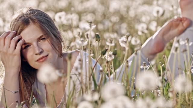 SLO MO Young woman lying among dandelions