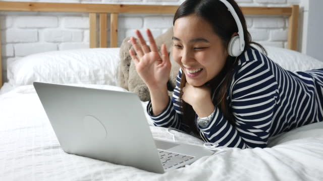 Young woman lying bed in a video call on laptop computer with headphone, Video Conference