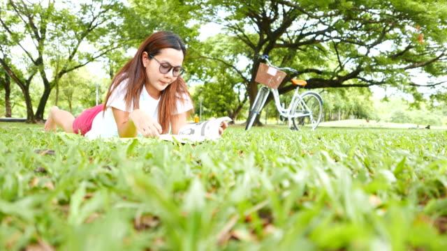 Junge Frau liegen und lesen Sie ein Buch im Park