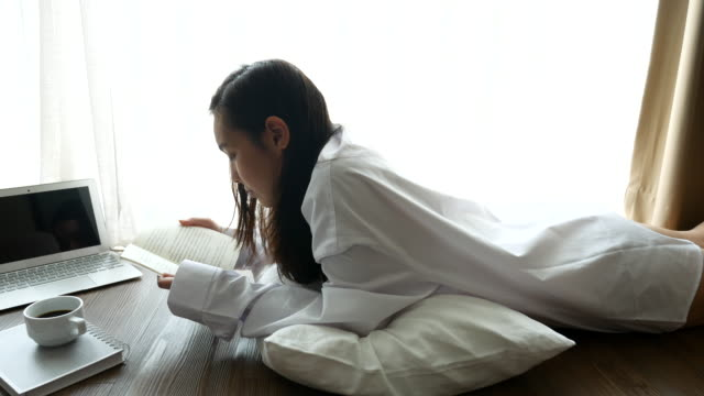 Young woman lying down reading and learning on the floor at home, Lifestyle concept, 4K(UHD)