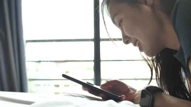 スマートフォンを使って横たわっている若い女性 - 見つける点の映像素材/bロール