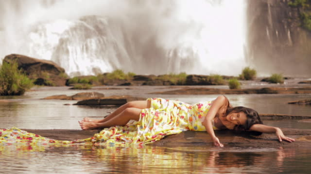 young woman lying near waterfall, athirappilly, kerala, india - auf der seite liegen stock-videos und b-roll-filmmaterial
