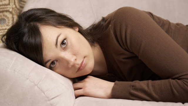 young woman lying on a couch - cardigan sweater stock videos & royalty-free footage