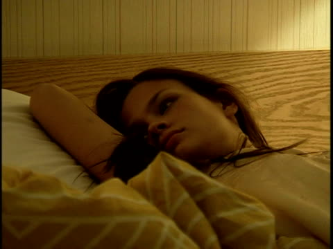 cu ds young woman lying on bed in motel room - knee highs stock videos and b-roll footage