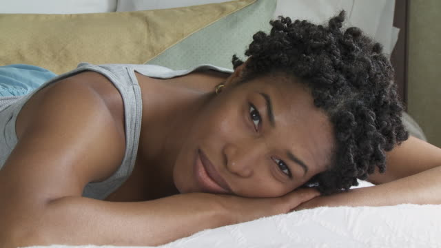stockvideo's en b-roll-footage met cu young woman lying on bed, smiling, portrait / new york city, new york, usa. - op de buik liggen