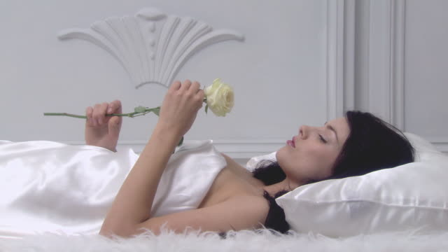 vídeos de stock, filmes e b-roll de young woman lying on bed with rose - cetim