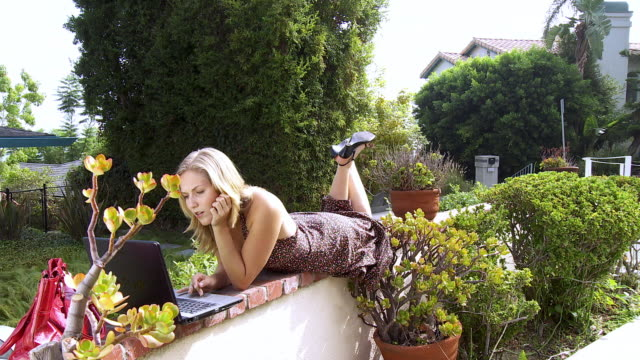 ws zi young woman lying on garden wall while using her laptop / sherman oaks, california, usa. - legs crossed at ankle stock videos and b-roll footage