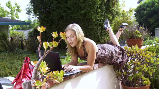 ws young woman lying on garden wall while using her laptop / sherman oaks, california, usa. - legs crossed at ankle stock videos and b-roll footage