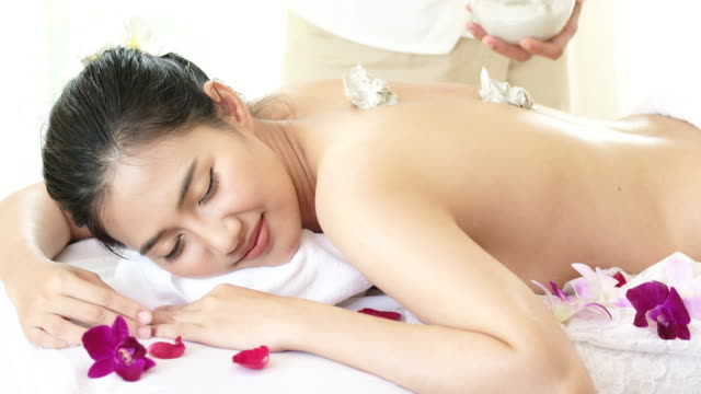 Young woman lying on spa bed and massage and clay body mask in spa for relax.