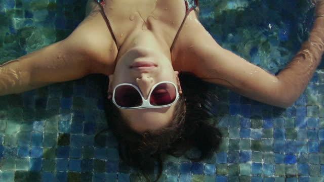 vídeos y material grabado en eventos de stock de zi, cu, ha, young woman lying on swimming pool steps, costa rica - gesticular