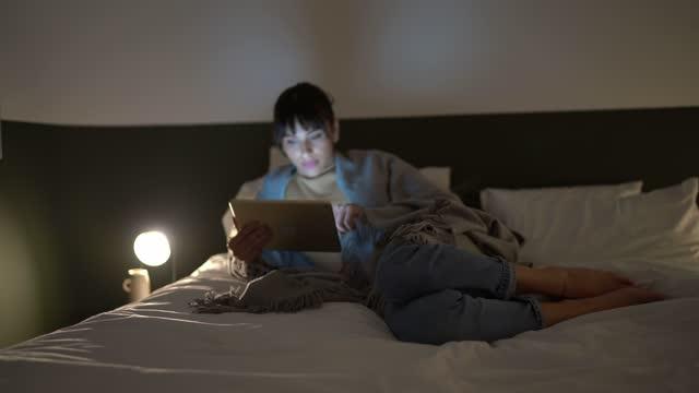 vídeos de stock, filmes e b-roll de jovem deitada na cama usando tablet digital em casa - quarto de dormir