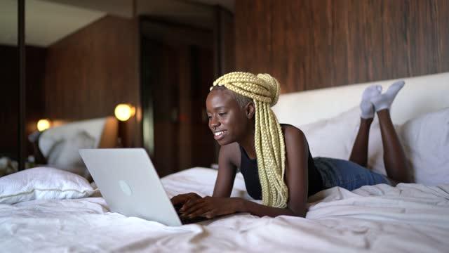 vídeos de stock, filmes e b-roll de jovem deitada na cama vlogging ou fazendo uma chamada de vídeo no laptop em casa - confortável