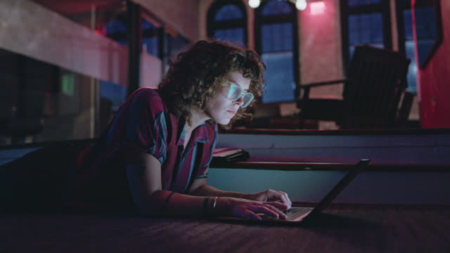 young woman lying on the floor works diligently on her laptop late into the night - using laptop stock videos & royalty-free footage