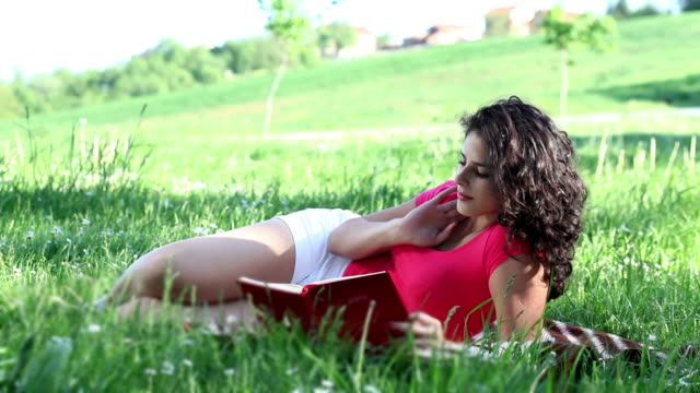 Young Woman lying on the grass and reading
