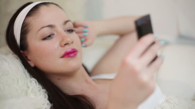 junge frau mit handy liegen - kosmetisches stirnband stock-videos und b-roll-filmmaterial