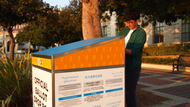 young woman mailing her ballot at the official pasadean ballot drop box - united states postal service stock videos & royalty-free footage