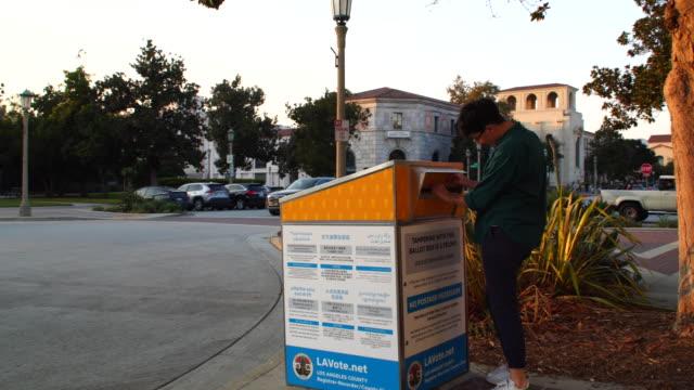 vidéos et rushes de jeune femme postant son bulletin de vote à l'urne officielle de pasadean - voie publique