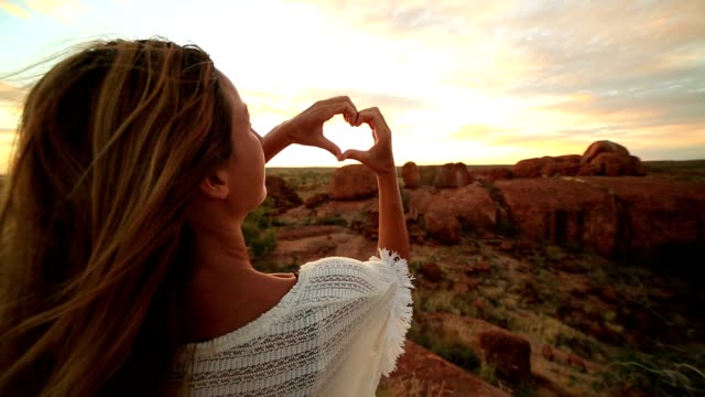 Young woman makes heart shape finger frame to spectacular landscape-sunrise
