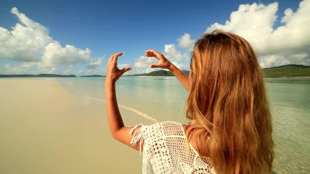Junge Frau macht Herzen Formrahmen Finger in Richtung Hill Inlet