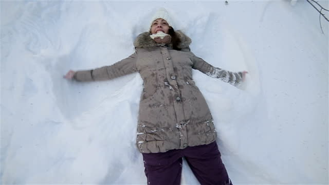 Young woman makes snow angel