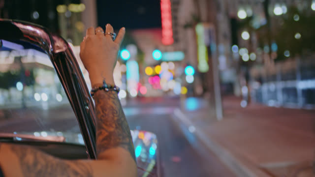 Young woman makes waves with her hand in classic convertible under downtown city lights.