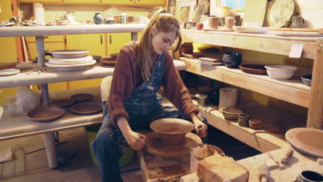 young woman making a bowl in her ceramics studio - skin feature stock videos & royalty-free footage