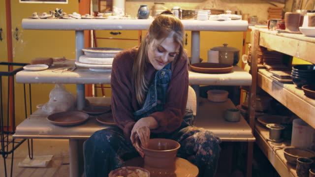 young woman making a bowl in her studio - pottery stock videos & royalty-free footage