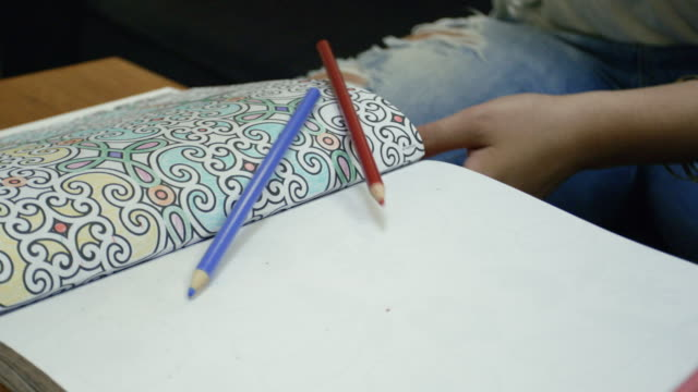 a young woman making a mess by dropping colored pencils on a coloring book - closeup - slow motion - 4k - lebanese ethnicity stock videos and b-roll footage