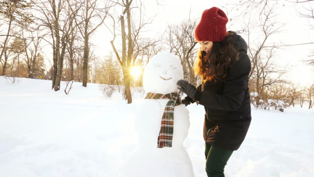 young woman making a snowman. - making a snowman stock videos & royalty-free footage