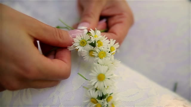 Young woman making beautiful wreath of daisies