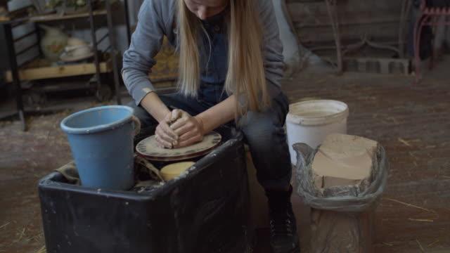 陶芸工房で陶芸を作る若い女性、中小企業のコンセプト - 陶芸家点の映像素材/bロール