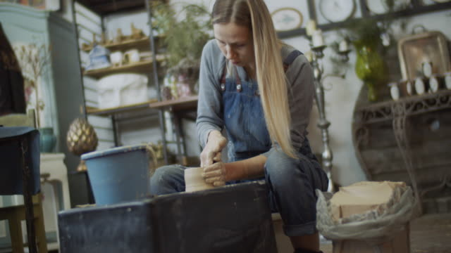 young woman making ceramics in her pottery workshop, small business concept - pottery stock videos & royalty-free footage