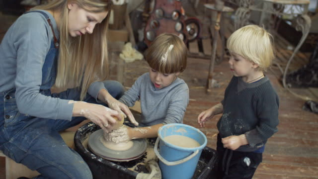young woman making ceramics on wheel in her pottery workshop, small business concept - pottery stock videos & royalty-free footage