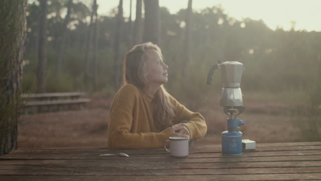 Young woman making coffee at picnic table at sunrise in the pine forest in the South of France.
