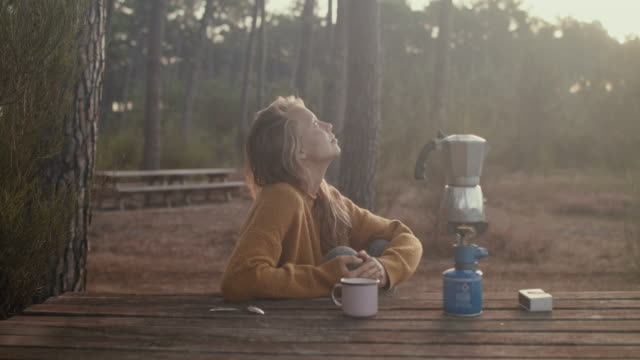 young woman making coffee at picnic table at sunrise in the pine forest in the south of france. - generation z stock-videos und b-roll-filmmaterial