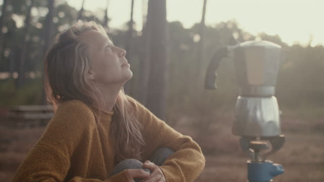 stockvideo's en b-roll-footage met young woman making coffee at picnic table at sunrise in the pine forest in the south of france. - naaldbos