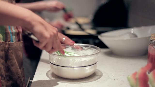 vídeos de stock, filmes e b-roll de jovem mulher fazer creme para panquecas - fogão