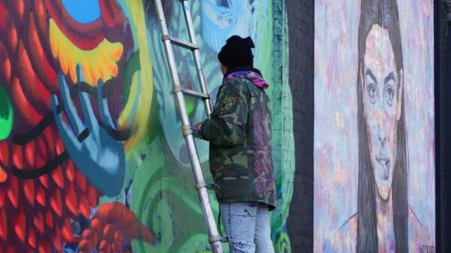 young woman making graffiti art in london shoreditch - graffiti stock videos & royalty-free footage