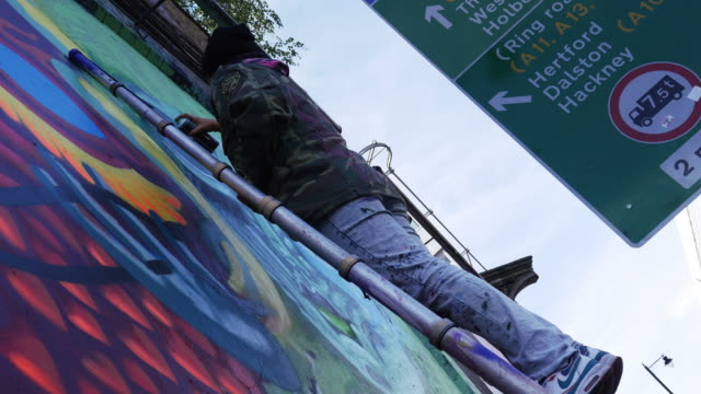 young woman making graffiti art in london shoreditch - graffiti stock videos & royalty-free footage