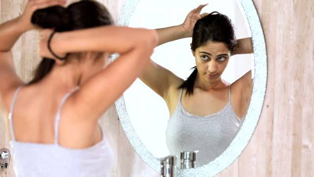 vídeos de stock, filmes e b-roll de young woman making hair bun in bathroom, delhi, india - coque cabelo para cima